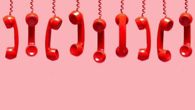 Various views of old red telephone receivers hanging on pink background