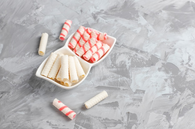 Various waffle rolls in ceramic plates,top view.