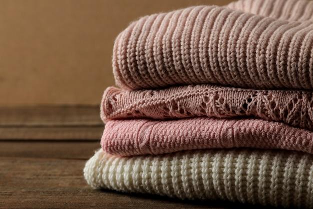 Различные теплые свитера сложены на коричневом деревянном фоне