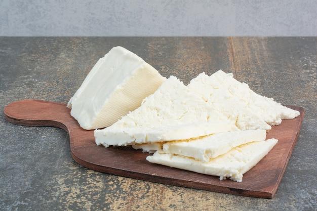 Различный белый сыр на деревянной доске.