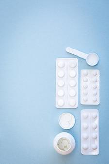 Различные белые таблетки на синем фоне