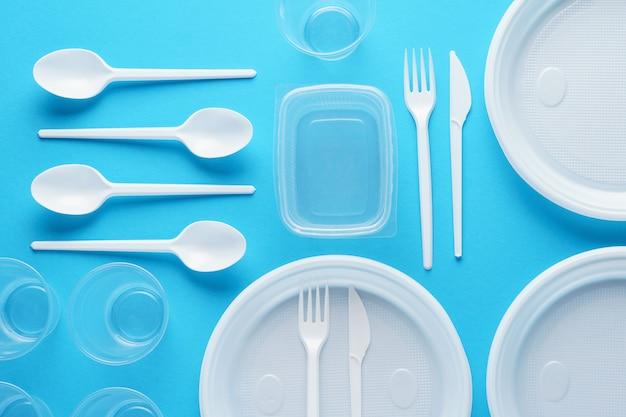 青い表面にさまざまな白いプラスチックの使い捨て食器。創造的なフラットレイアウト。