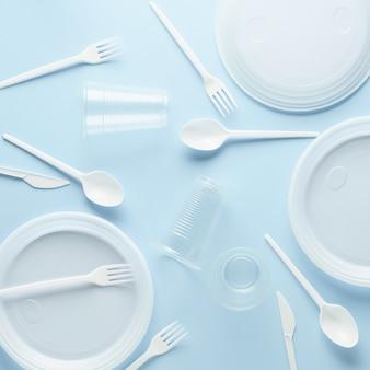 パステルブルーの表面にさまざまな白いプラスチック製の使い捨て食器。創造的なフラットレイアウト。