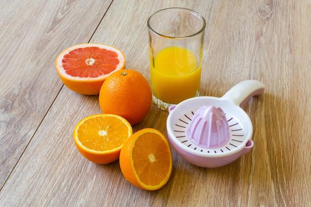 다양한 전체 및 절단 감귤류 과일 수동 리머와 나무 테이블에 오렌지 주스 한 잔