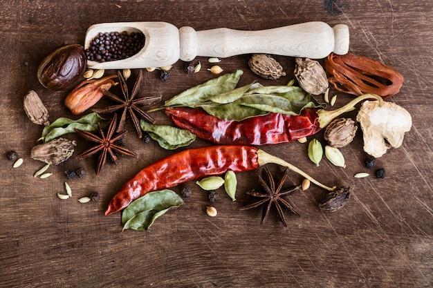 木製のテーブルに様々な全体のインドのスパイス。