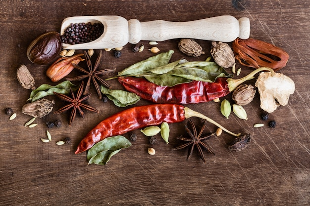 Various whole indian spices on wooden table.
