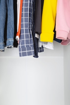 Various women's clothes hang in white closet