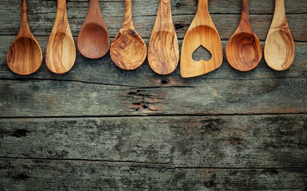 Various wooden cooking utensils on shabby wooden background .