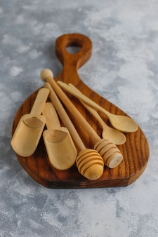 Various wooden spoons with handmade wooden cutting board on grey concrete