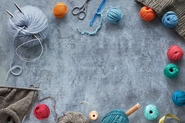 Various wool yarn and knitting needles, creative knitting hobby background with copy-space