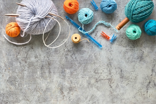 Various wool yarn and knitting needles, creative knitting hobby background with text space