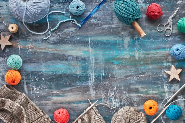 Various wool yarn and knitting needles, knitting hobby background, copy-space