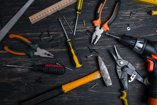 Various working tool on a dark wooden table.