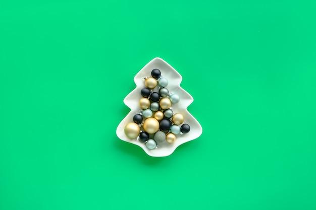민트 녹색 종이에 전나무 모양의 접시에 다양한 크리스마스 싸구려, 크리스마스 카드 또는 배너에 대한 최신 유행 미니멀 디자인