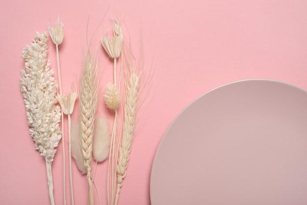 ピンクのテーブルにさまざまな黄色の乾燥した野花。上面図