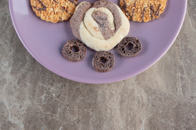 Variously cookies and corn rings on a plate on marble.
