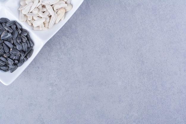 Varie semi in una ciotola, sul marmo.