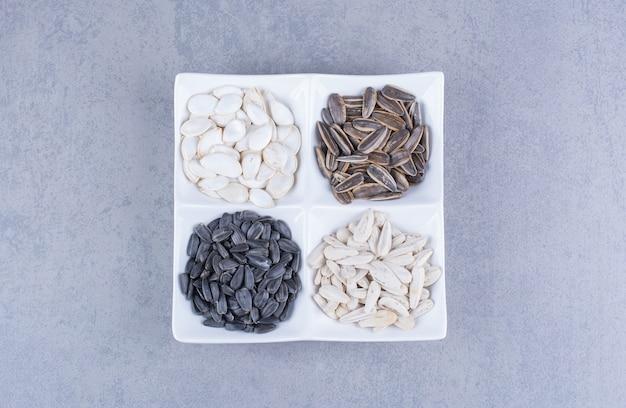 По-разному семена в миске на мраморе.