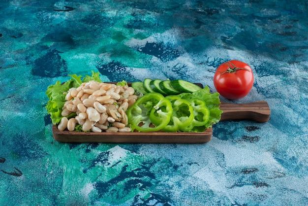 青いテーブルのボードにさまざまな野菜や豆。