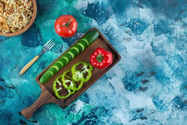 青いテーブルの上の麺のボウルをフォークする隣のボード上のさまざまな野菜。