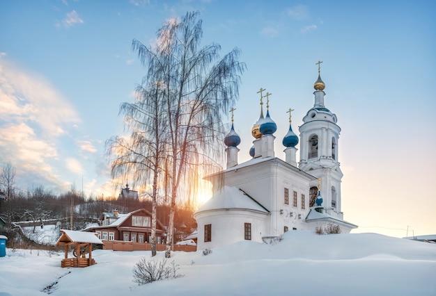 Варварская церковь с колокольней и гора левитана в плесе в снегу в свете заходящего зимнего солнца.