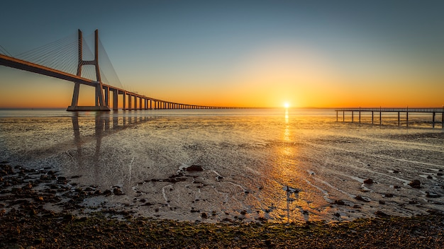 Мост васко де гама на рассвете с восходом солнца