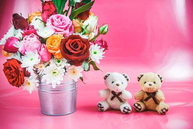 Vase of bouquet roses and lovely couple bear on pink background