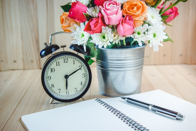 Vase bouquet roses near black vintage clock and notebook