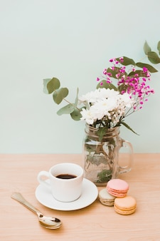 Vase; cup of coffee; spoon and macaroons on wooden table against colored background