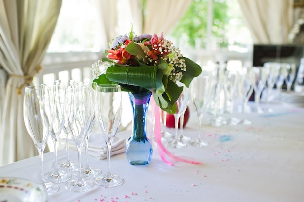 Vase decorated with fresh flowers at the wedding banquet.
