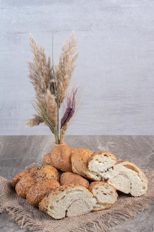 Vase of decorative wheat stalks next to bundle of sesame coated, sliced bread loaves on marble background. high quality photo