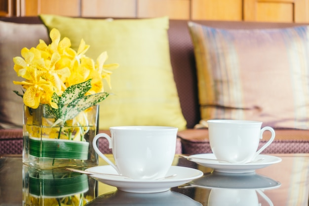 Vase flower and white coffee cup on table and pillow on sofa