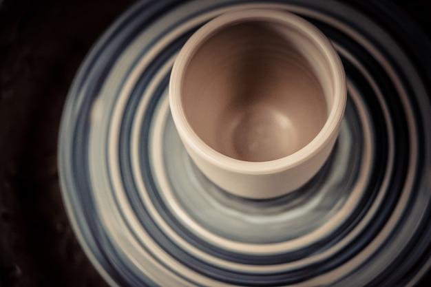 新鮮な粘土からの花瓶は、ろくろを回転させます