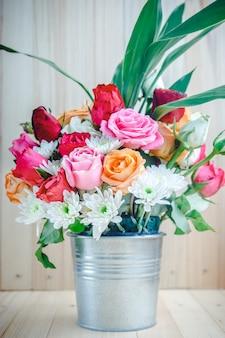 アルミ製のバケツでバラの花束の花瓶