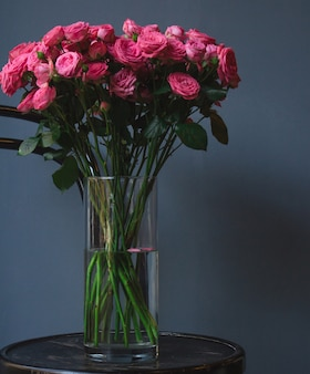 A vase of pink roses standing on an old rustic round ottoman chair