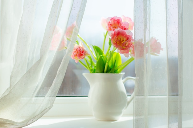 A vase of pink tulips  on the window