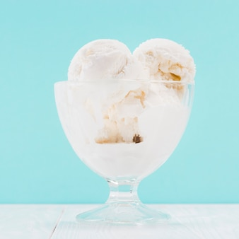 Vase of vanilla ice cream on blue background