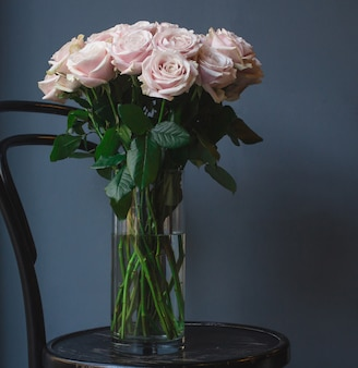 A vase of white pastel tone roses standing on an old rustic round ottoman chair
