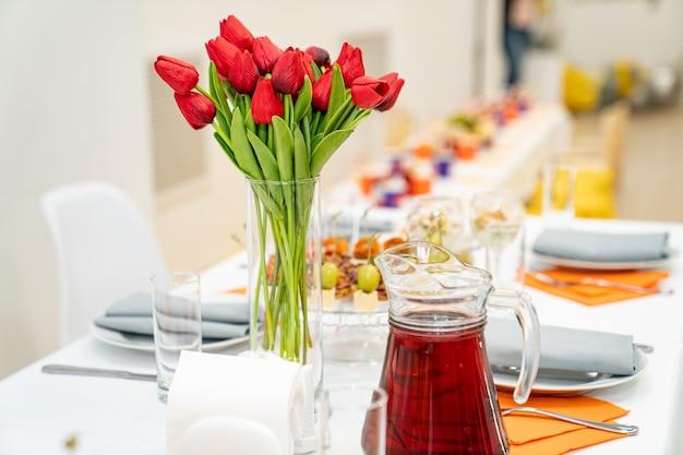 Ваза с букетом красных тюльпанов на праздничном столе. сервировка стола с закусками, канапе, салатами в банках. питание. ресторанный бизнес.