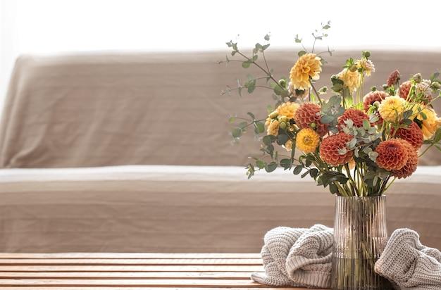 Ваза с букетом желтых и оранжевых хризантем в интерьере комнаты на размытом фоне.