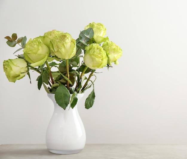 光に対してテーブルの上に緑のバラの美しい花束と花瓶