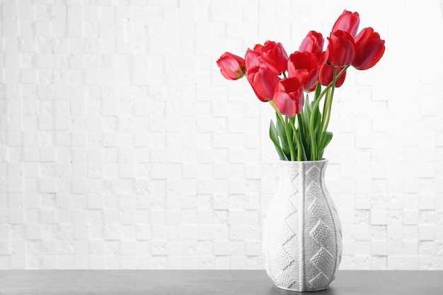 Vase with beautiful flowers on table against light background