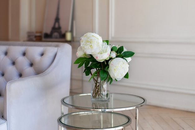 Vase with beautiful peony flowers on table near a grey sofa in living room
