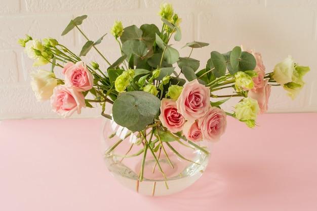 テーブルの上に美しいバラ、トルコギキョウ、ユーカリの花が付いた花瓶。休日の入札グリーティングカード。