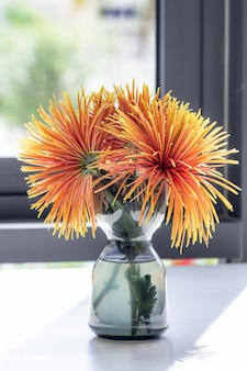 Vase with beautiful yellow chrysanthemum flowers on a table.