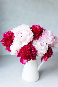 Vase with bouquet of beautiful peonies on table in room, close-up