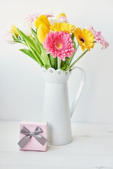 Vase with bouquet of beautiful tulips and gerberas with pink gift box