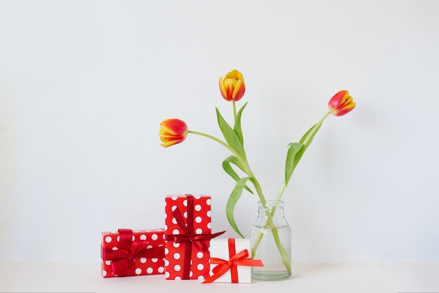 A vase with a bouquet of beautiful tulips and gift boxes on the table