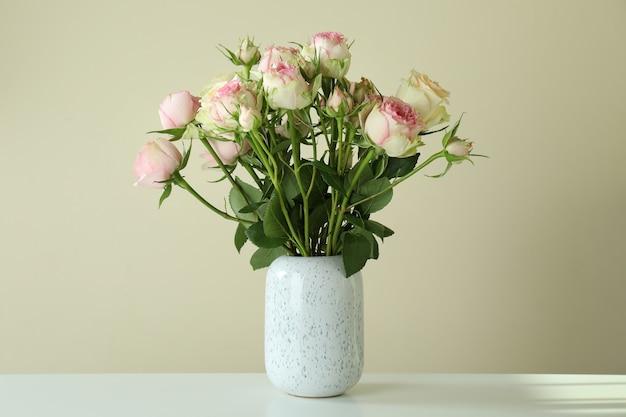白いテーブルの上のバラの花束と花瓶