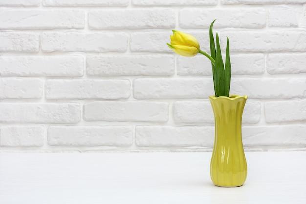 흰색 장식 벽돌 벽에 튤립 꽃다발이 있는 꽃병